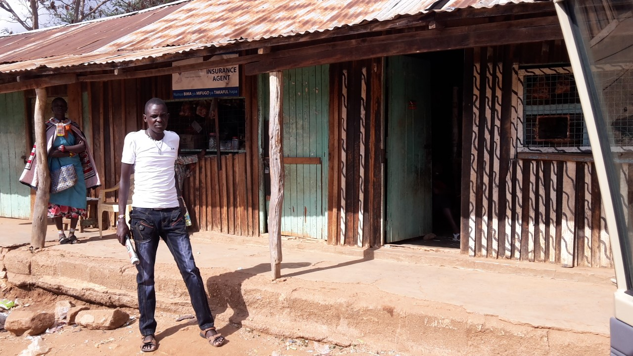 An agent for Takaful Insurance of Africa stands outside his shop. Courtesy of IBLI.