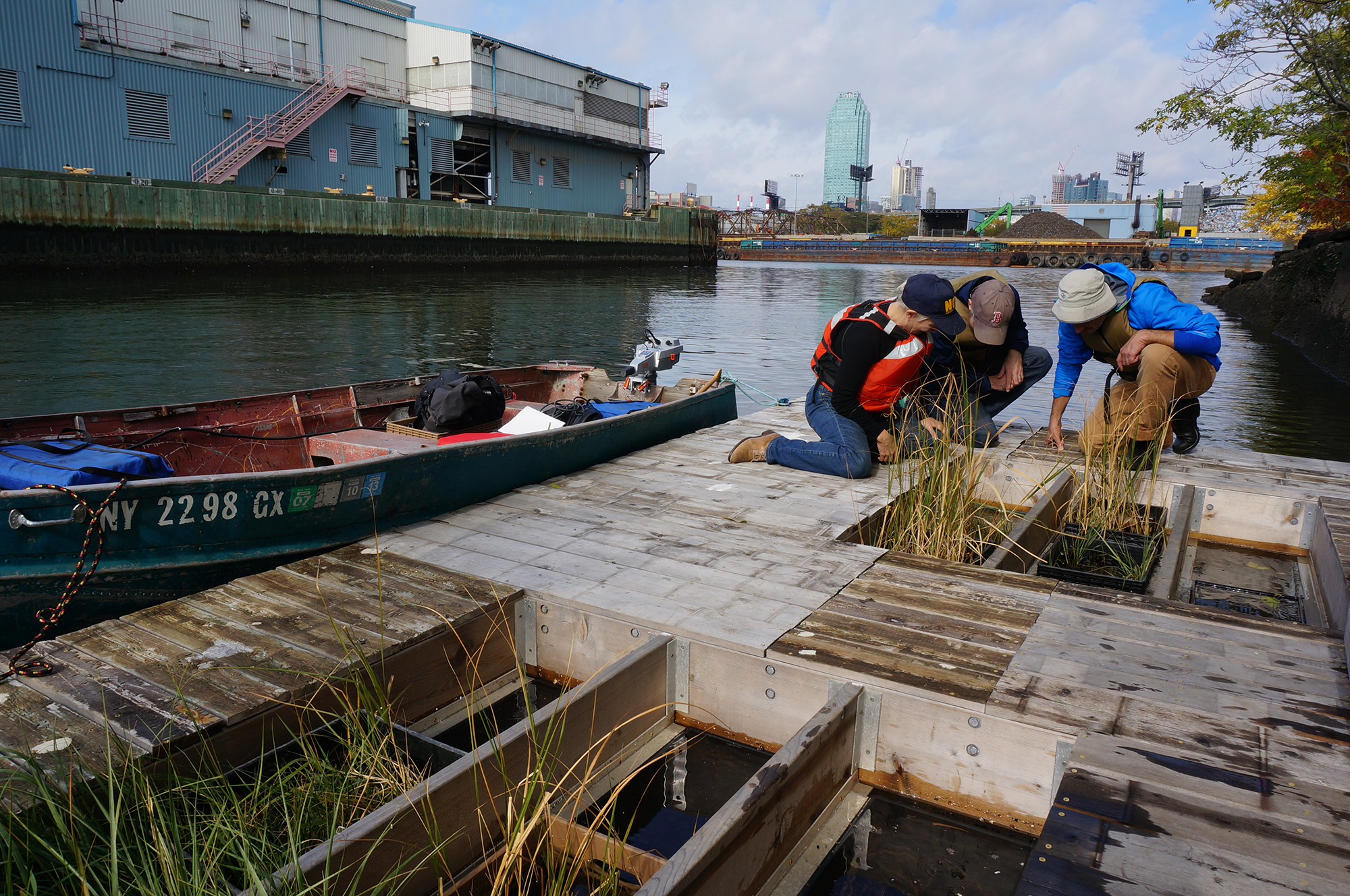 Researchers check one of the constructed floating wetlands on Newtown Creek. Students and volunteers monitor the grasses, which filter pollutants from the water. Image courtesy of Newtown Creek Alliance.