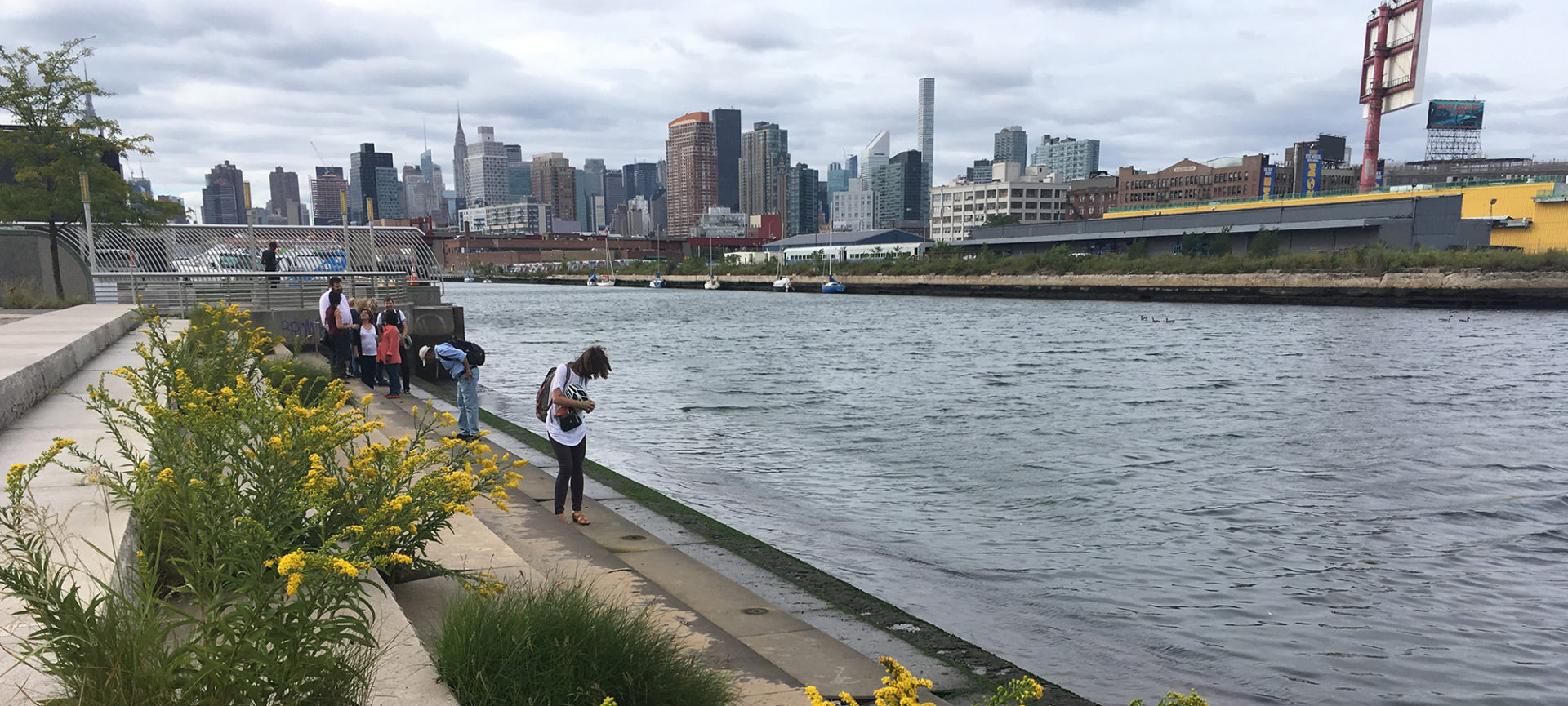 On the Newtown Creek waterfront, with industrial landscape and Manhattan. Image courtesy of the Newtown Creek Alliance.