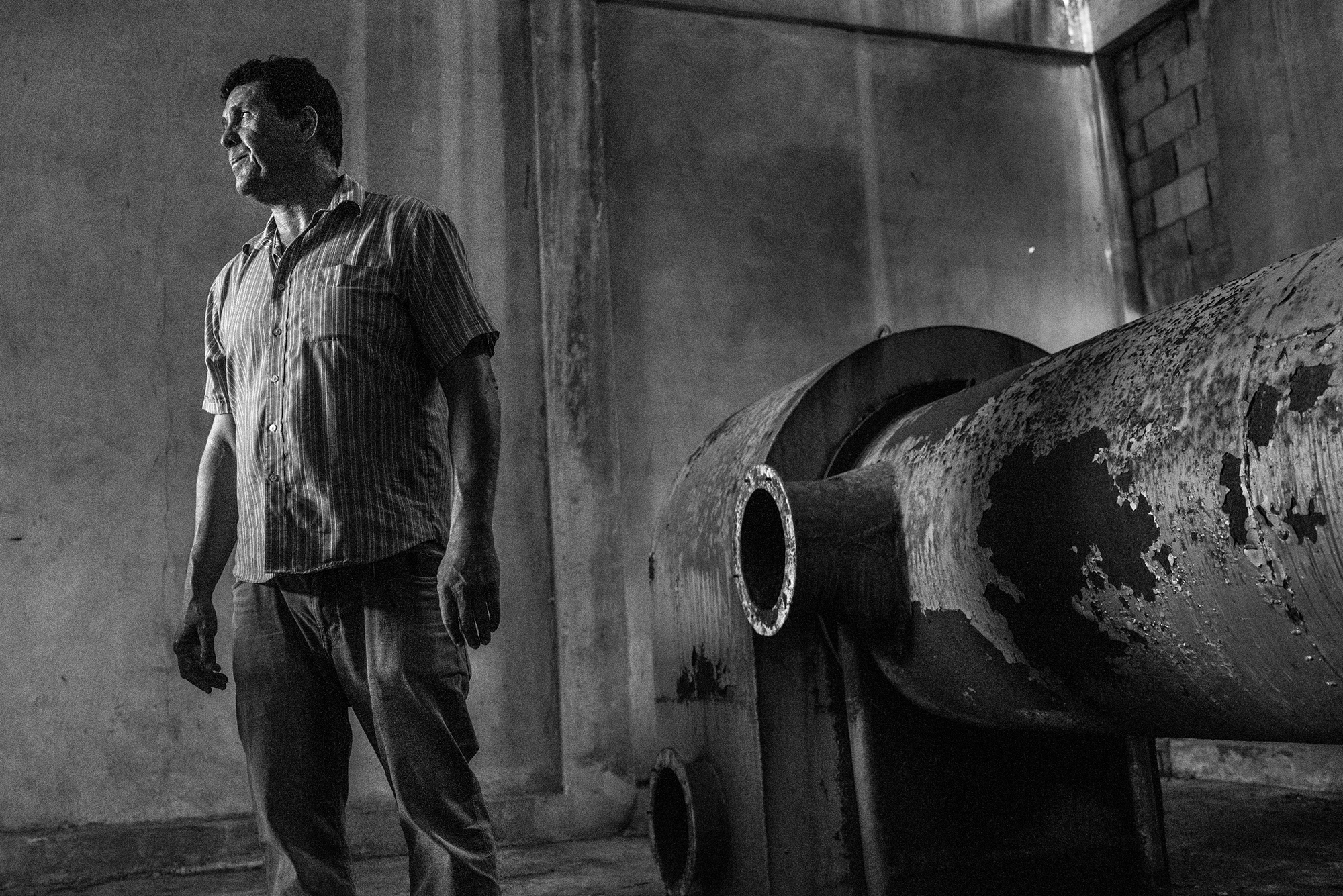 Tito Valentín, a community leader in Utuado, Puerto Rico, stands inside an old coffee-processing plant, which he hopes to revitalize for agro-tourism. Photo: Rebecca Kiger.