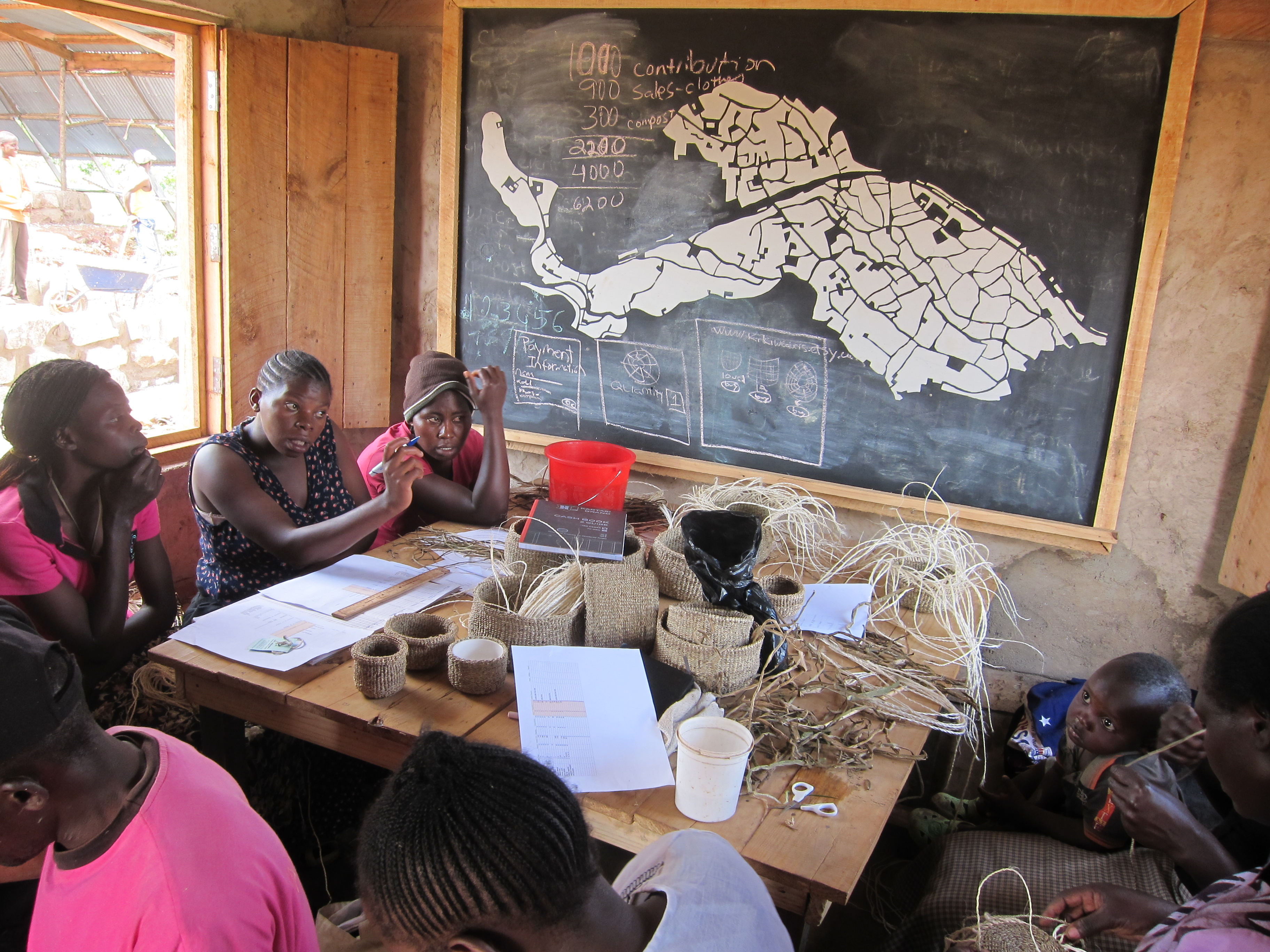 Women from NNDC group's weaving cooperative discuss management issues in the site office. Credit: KDI.