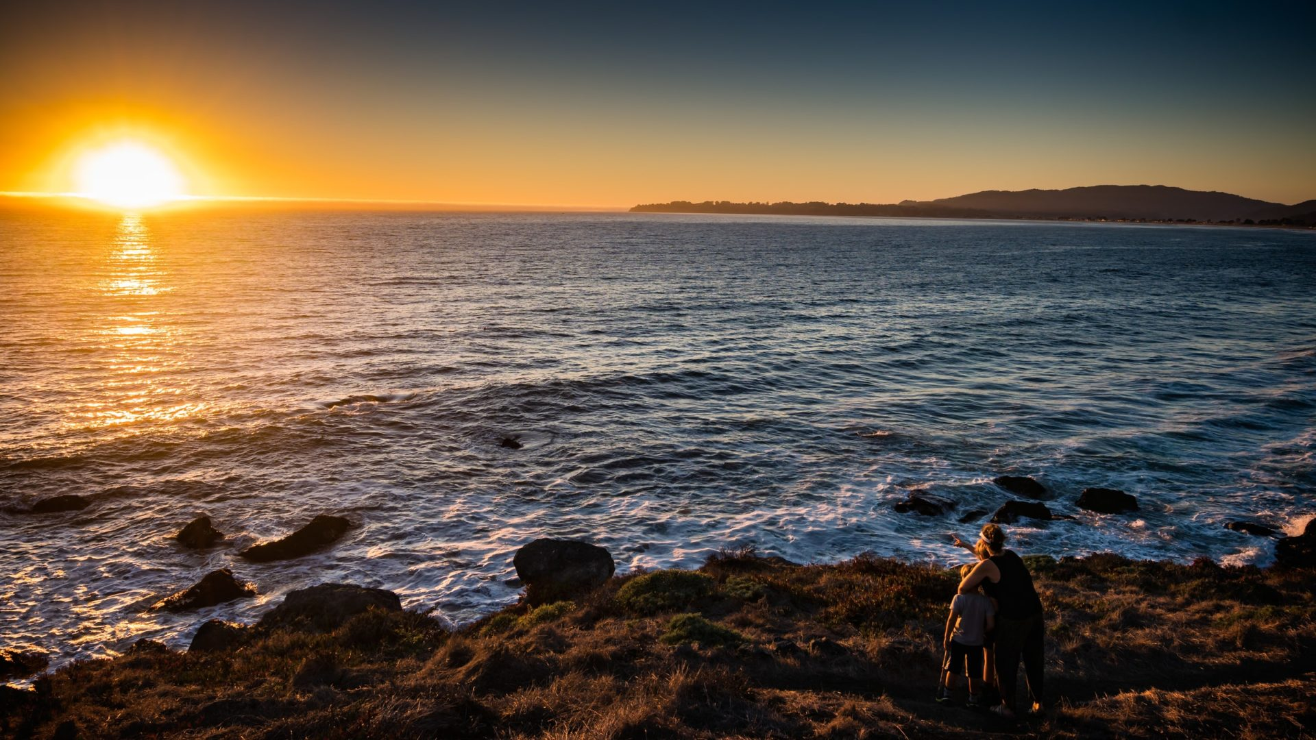 Woman and children standing in front of ocean sunset